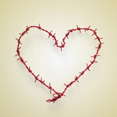 heart-shaped roll of barbed wire on a beige , with a retro effect photo