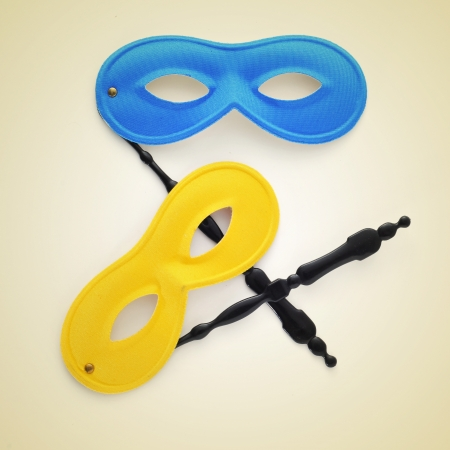 fancy dress party: some carnival masks on a beige background, with a retro effect