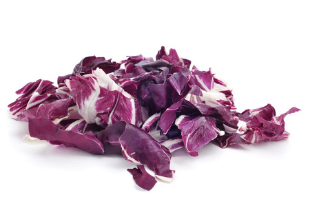 radicchio: closeup of a pile of chopped radicchio leaves on a white background