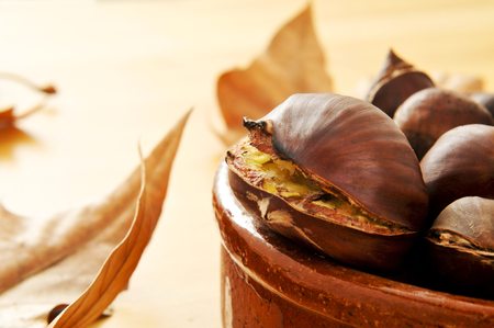 closeup of some roasted chestnuts in an earthenware bowl and autumn leaves in the background photo