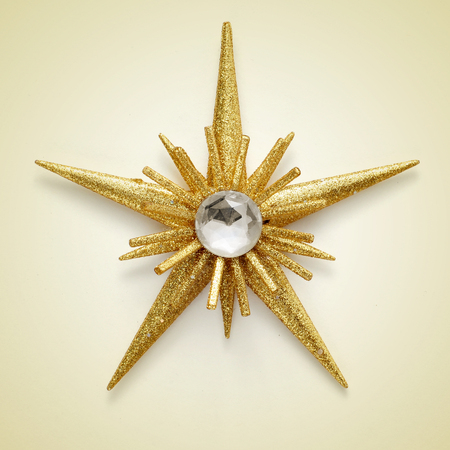 a golden christmas star on a beige background with a retro effect photo