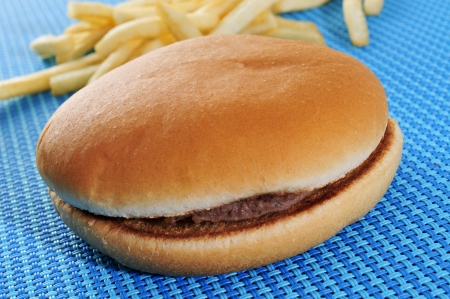 appetizing hamburger sandwich and fries on a set table photo