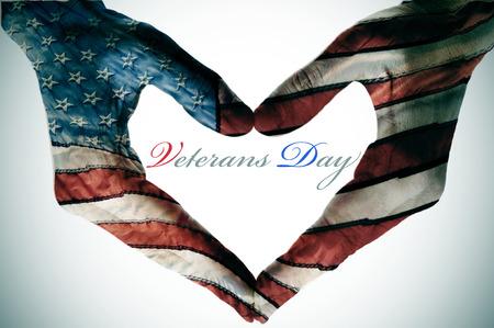 day: Día de los Veteranos escrito en el espacio en blanco de una señal de corazón hecha con las manos estampadas con los colores y las estrellas de la bandera de Estados Unidos Foto de archivo