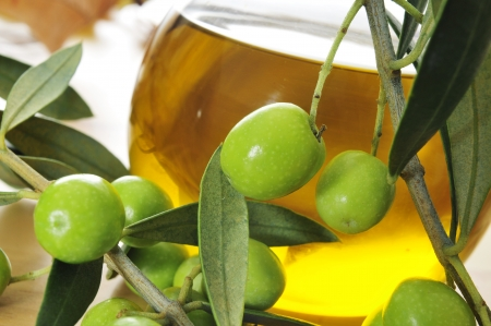 closeup of a branch of olive tree with olives and a bottle of olive oil in the background photo