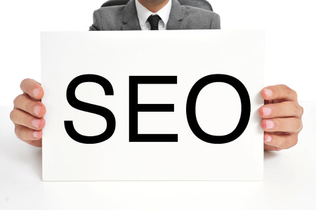 a man wearing a suit holding a signboard with the word SEO, acronym for Search Engine Optimization, written in it photo