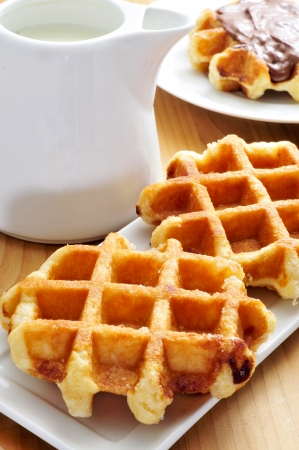 a pot with milk and some waffles in a plate, on a wooden table Stock Photo