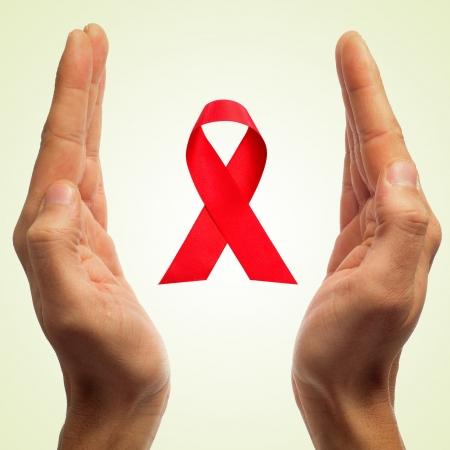 man hands and a red ribbon for the fight against AIDS Stock Photo - 23250740