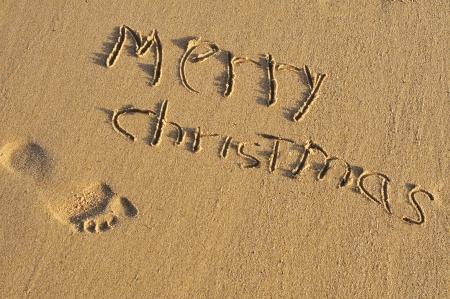sentencia: frase feliz navidad escrito en la arena de una playa Foto de archivo