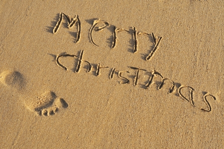 sentence merry christmas written on the sand of a beach photo