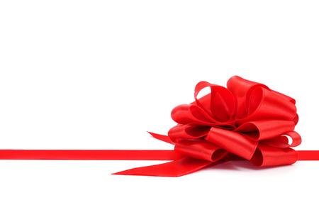 lazo regalo: una cinta roja con un arco sobre un fondo blanco, con copia espacio en blanco Foto de archivo