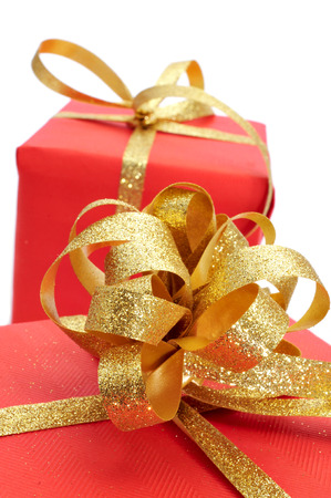 some gifts wrapped with red wrapping paper and with a golden ribbon on a white background  photo