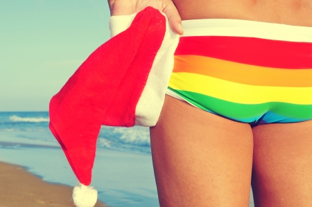 someone at the beach wearing a rainbow swimsuit and holding a Santa hat in his hand photo