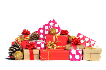 some christmas gifts wrapped with wrapping paper of different colors and ribbon bows, and some christmas ornaments on a white background Stock Photo - 23385787