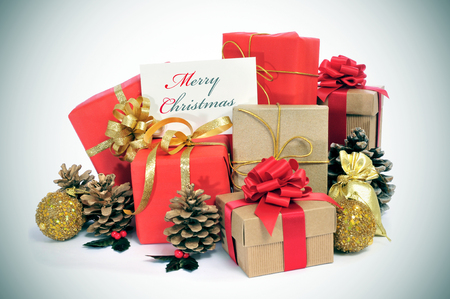 some christmas gifts wrapped with wrapping paper of different colors and ribbon bows, and some christmas ornaments, and a signboard with the sentence merry christmas written in it Stock Photo - 23385811