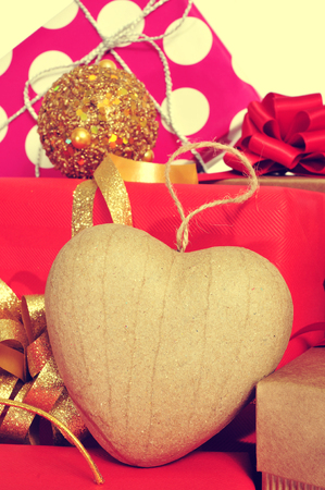 closeup a heart-shaped ornament and some christmas gifts wrapped with wrapping paper of different colors and ribbon bows, with a retro effect photo