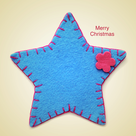 picture of a christmas star and the sentence merry christmas written on a beige background, with a retro effect photo
