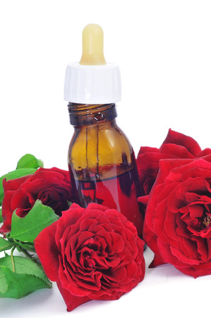perfumer: closeup of a dropper bottle with rose essence with red roses on the background