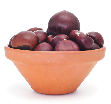 tots: an earthenware bowl with chestnuts on a white background