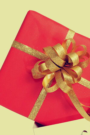 a gift wrapped with red wrapping paper and with a golden ribbon, in a shopping bag, with a retro effect photo