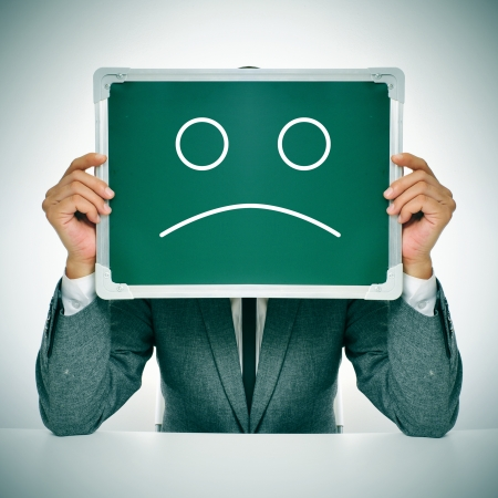 ruination: man wearing a suit sitting in a table holding a blackboard in front of his head with a sad face drawn in it