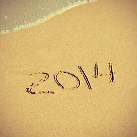 the number 2014, as the new year, written in the sand of a beach photo