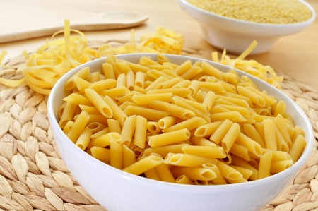 some different uncooked pasta, such as penne rigate, tagliatelle and pastina, on a table photo