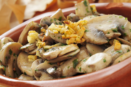 cooked mushrooms with garlic and parsley in an earthenware bowl photo