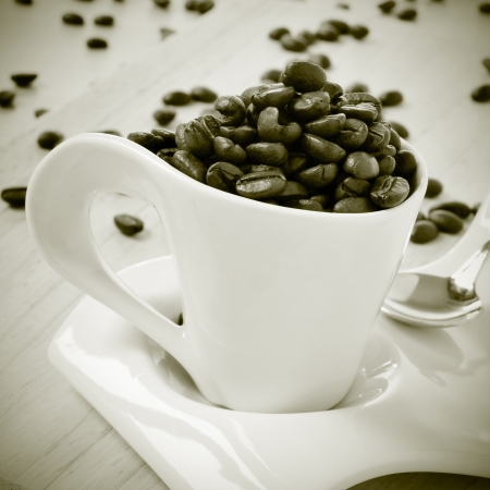 closeup of a cup of coffee full of roasted coffee beans on a wooden table, in black and white photo