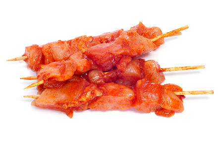 skewed: closeup of some raw spiced chicken meat skewers, on a white background