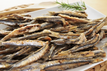 engraulis: closeup of a plate with spanish boquerones fritos, battered and fried anchovies typical in Spain