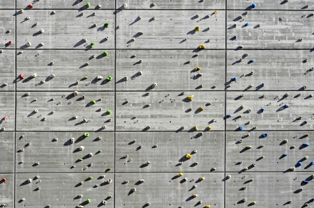 detail of a concrete climbing wall with grips for hands and feet photo