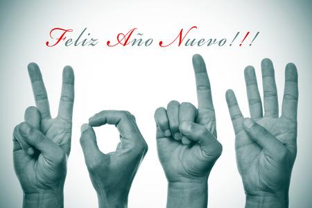 oracion: frase feliz ano nuevo, feliz a�o nuevo escrito en espa�ol, y las manos formando n�mero 2014