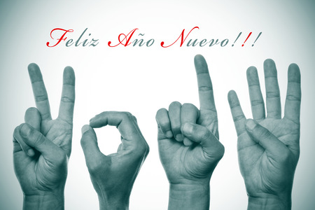 nuevo: sentence feliz ano nuevo, happy new year written in spanish, and hands forming number 2014 Stock Photo