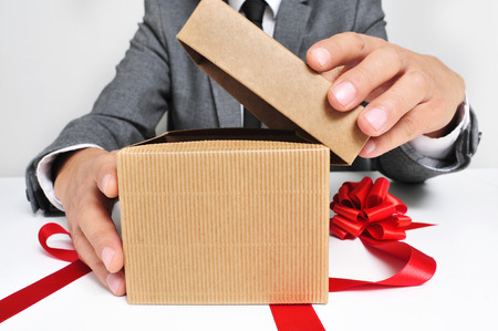 man wearing a suit sitting in a table opening a gift with a red ribbon photo