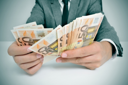a man wearing a suit sitting in a desk counting euro bills photo