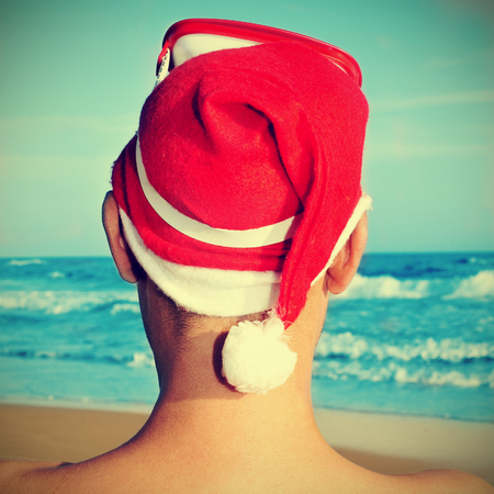 picture of someone on the beach wearing a Santa hat and a diving mask in his head, with a retro effect photo