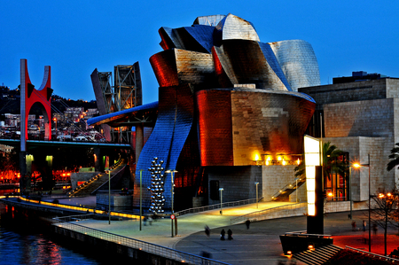 Bilbao, Spain - November 14, 2012  The Guggenheim Museum and the estuary at evening in Bilbao, Spain  This picturesque and futuristic museum was designed by Frank Ghery