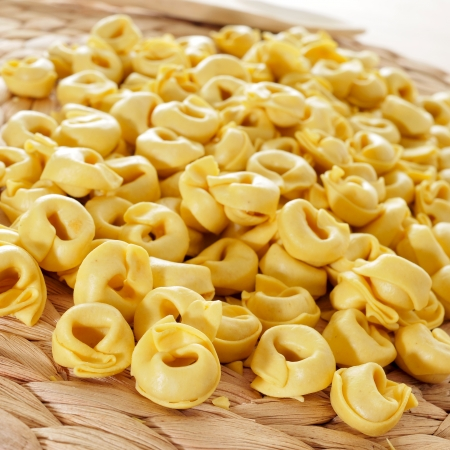 stuffed tortellini: closeup of a pile of uncooked tortellini Stock Photo