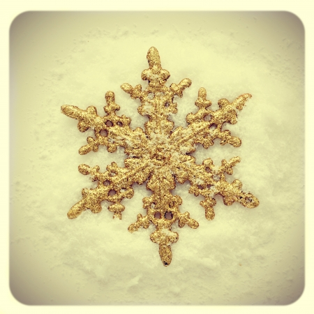 picture of a golden snowflake-shaped christmas star on the snow with a retro effect photo