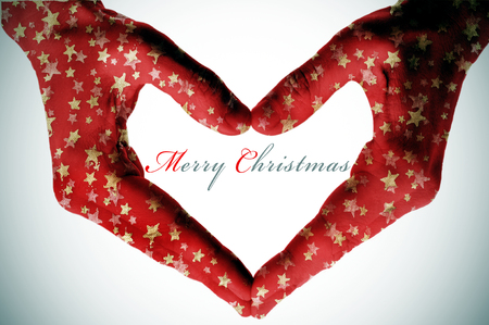 hands patterned with golden christmas stars forming a heart and the sentence merry christmas  photo