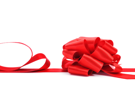 a red satin ribbon with a bow on a white background photo