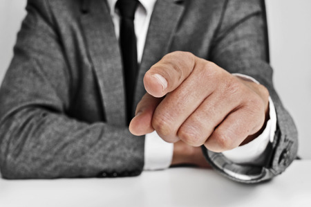 incriminate: man wearing a suit sitting in a table pointing the finger to the observer