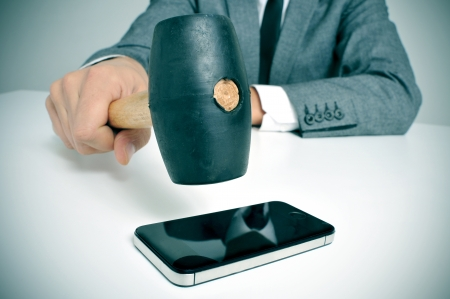 annoy: a businessman sitting in a table with a hammer in his hand ready to crash it on a smartphone Stock Photo