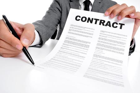 firmando: hombre que llevaba un traje sentado en una tabla de un contrato y que el firmante debe firmar Foto de archivo