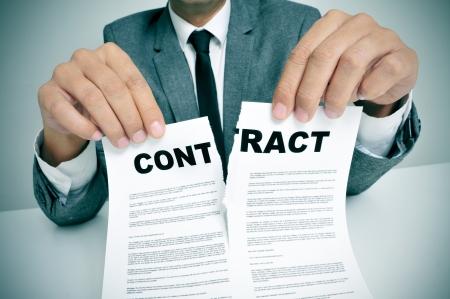 contrato de trabajo: hombre que llevaba un traje sentado en una mesa que rasga un contrato