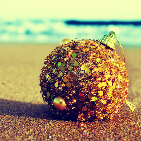 hemisphere: picture of a golden christmas ball on the sand of a beach, with a retro effect Stock Photo