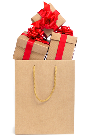some gifts with red ribbon bows in a shopping bag photo