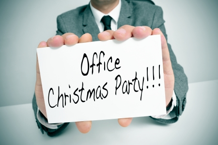 company party: a man wearing a suit sitting in a desk holding a signboard with the text office christmas party written in it