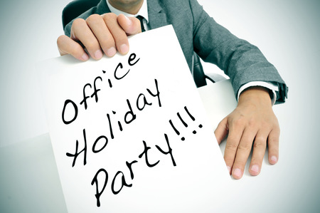 a man wearing a suit sitting in a desk holding a signboard with the text office holiday party written in it