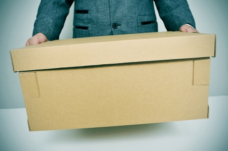 demotion: a businessman carrying a box, leaving or moving to a new office